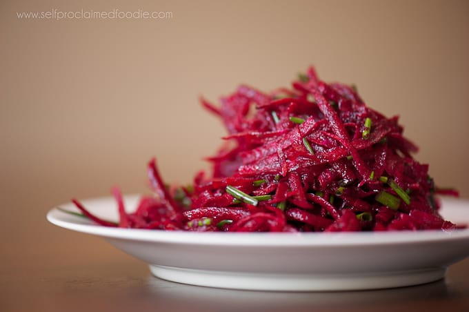 raw beet salad with citrus vinaigrette on white plate