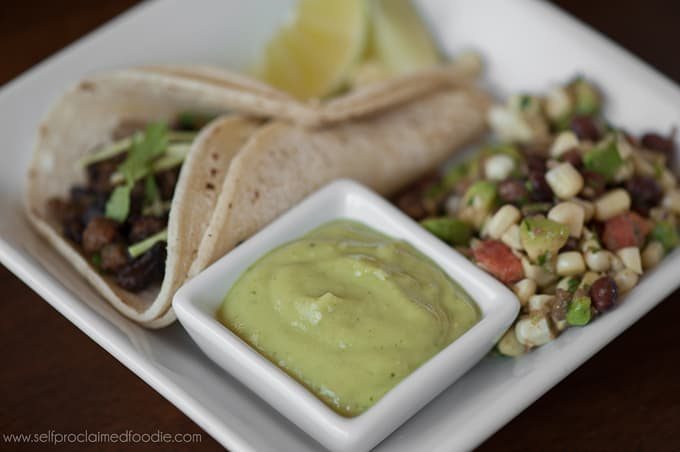 avocado tomatillo salsa on plate with taco and corn side salad