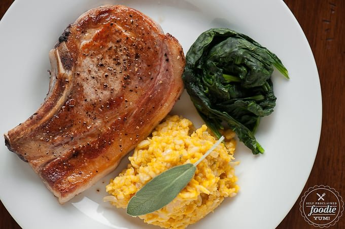 salt and pepper Pork chop on plate with spinach and butternut risotto