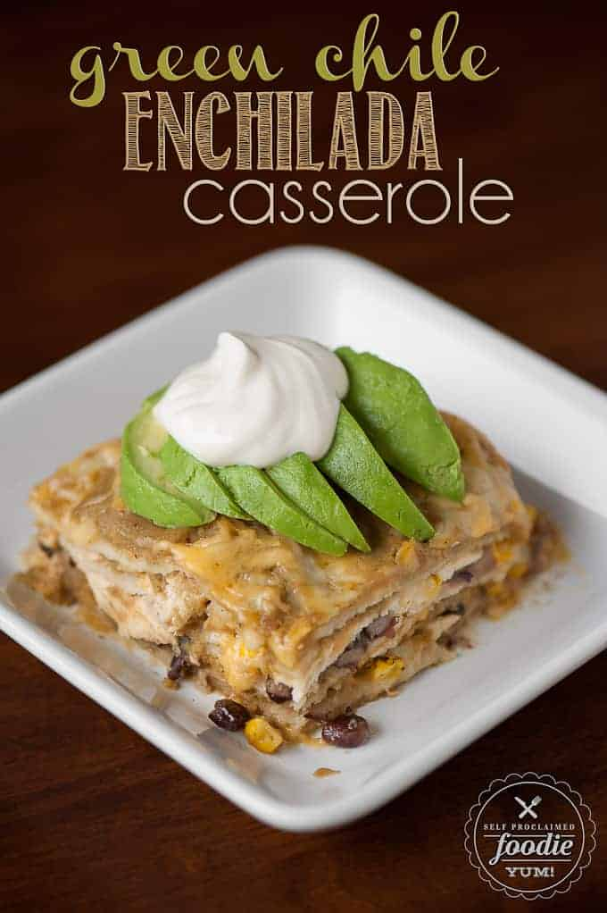 green chile enchilada casserole on plate topped with avocado and sour cream