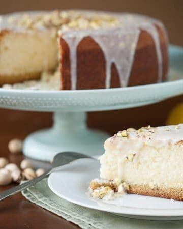 This sweet and rich Lemon Pistachio Cake is sure to impress with its pistachio cookie crust, melt-in-your-mouth lemon cake, and lemon zest icing.