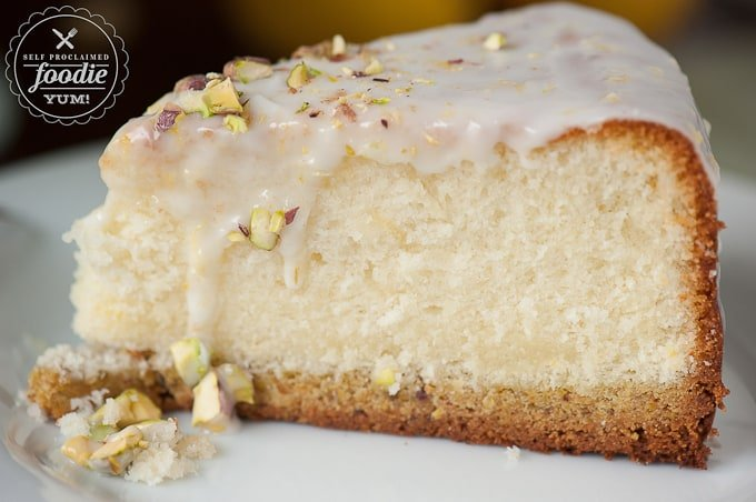 a close up of a slice of glazed pistachio lemon cake