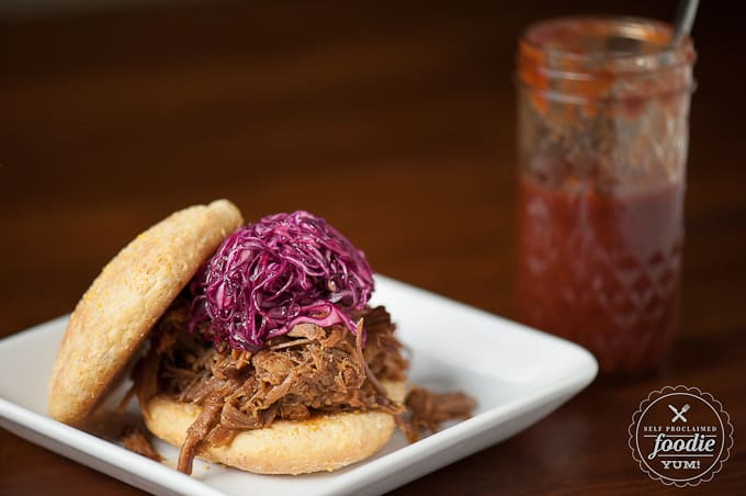 pulled pork sandwich topped with purple cabbage slaw and bbq sauce
