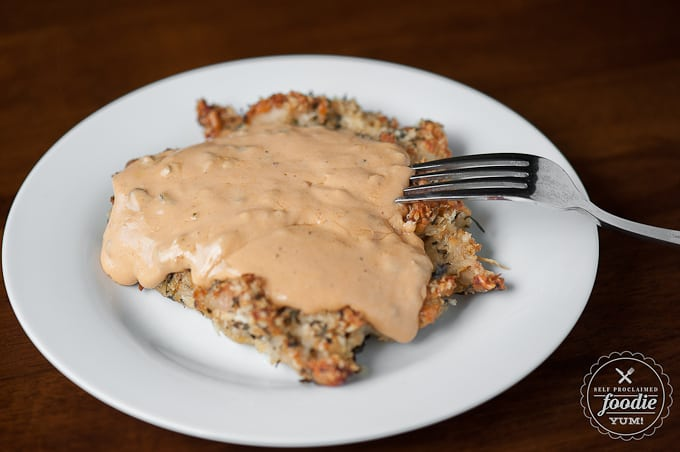 breaded chicken breast covered in cheese sauce on plate