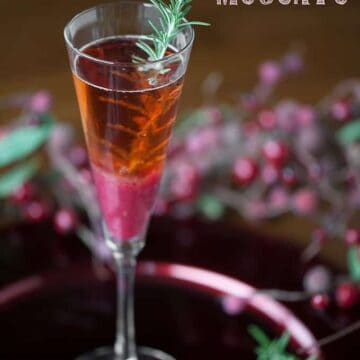 champagne flute with a cranberry pear moscato cocktail with rosemary garnish