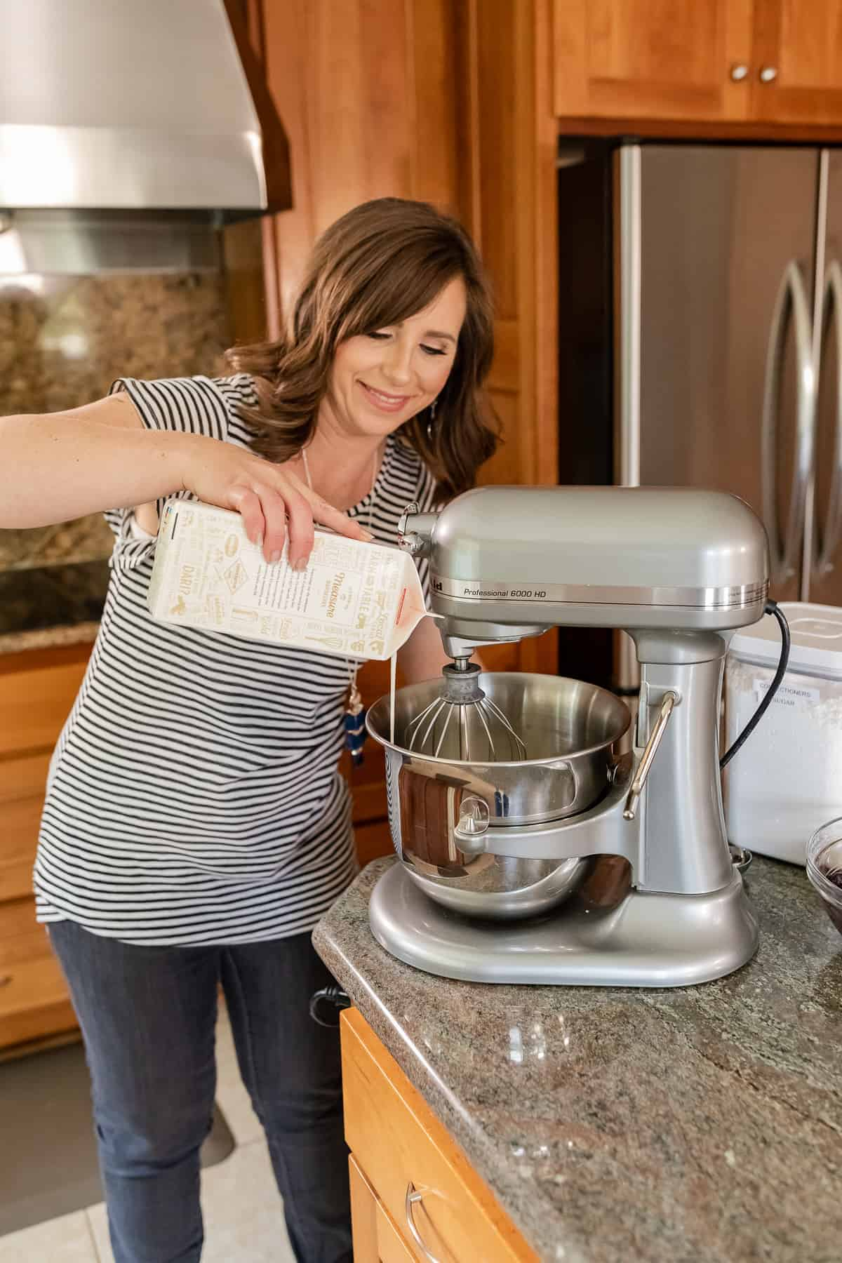 krissy allori pouring heavy cream into a stand mixer bowl