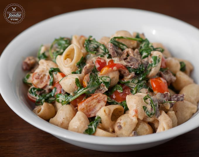 BLT Pasta made with your favorite pasta, cooked cherry tomatoes, garlic, arugula, and bacon in a cream sauce is an easy and delicious meal time solution.