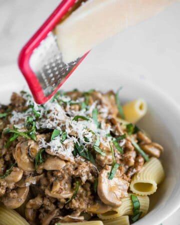 grating parmesan cheese over bowl of sausage mushroom rigatoni