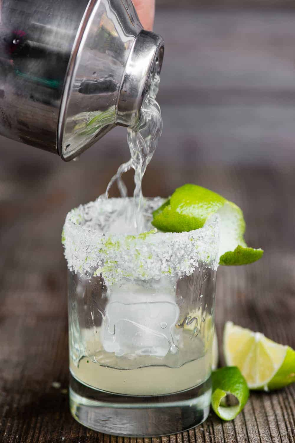 pour a classic margarita out of cocktail shaker into glass