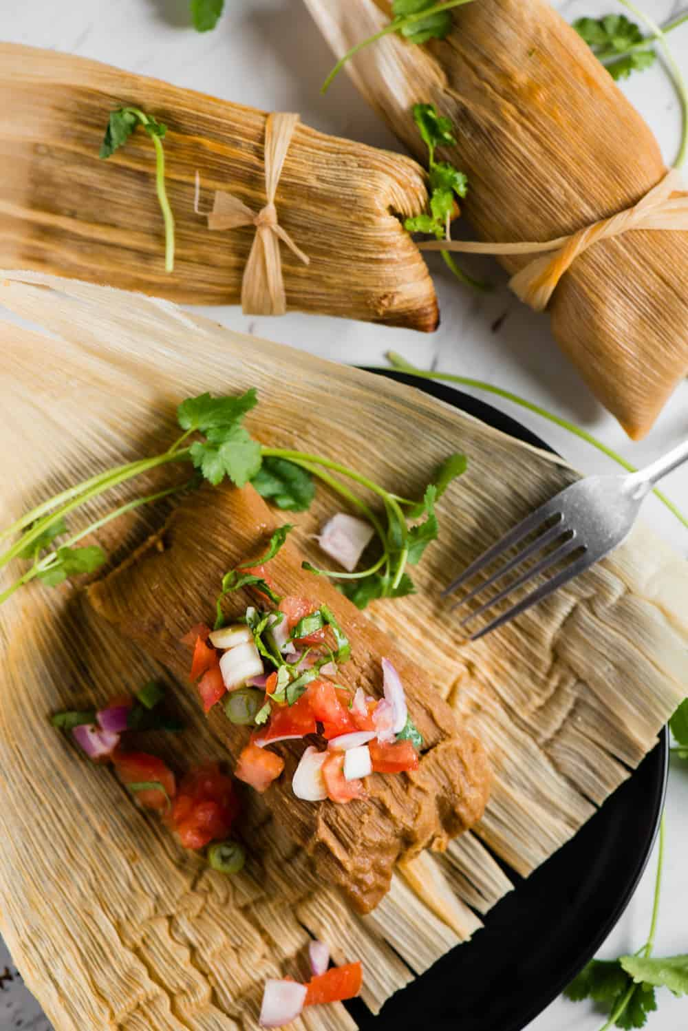 instant pot pork tamales on corn husk with salsa