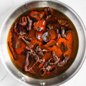 browned red chiles soaking in boiling water