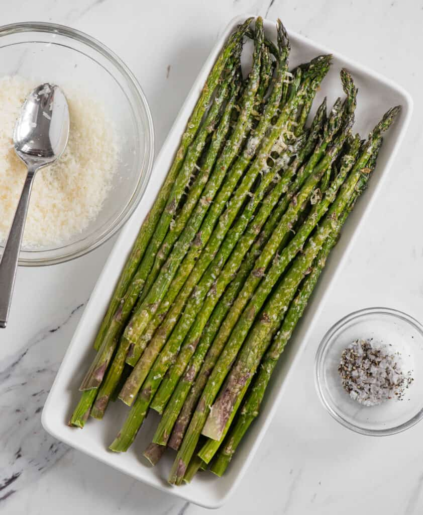 asparagus spears on rectangular platter with parmesan cheese in bowl