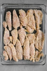 coated chicken tenders in air fryer basket
