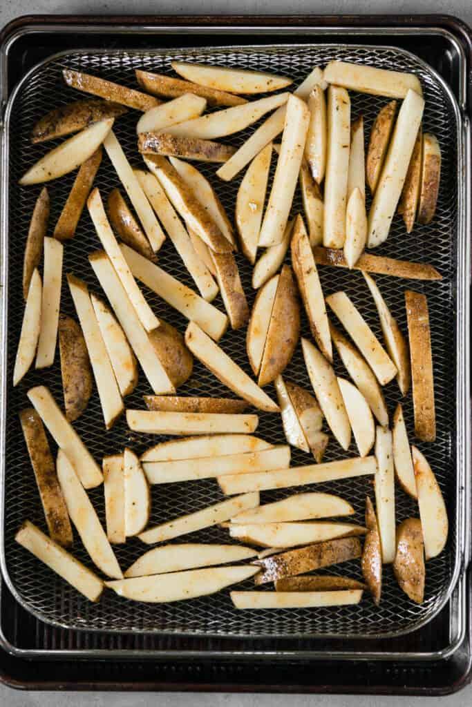 seasoned potatoes on air fryer basket
