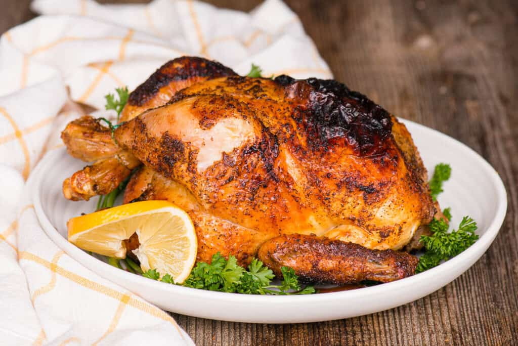 Air Fryer Whole Chicken on platter with lemon and parsley