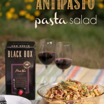 pasta salad  in bowl with box of wine and two wine glasses