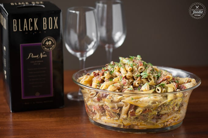 a bowl of antipasto pasta salad with wine glasses and box of wine