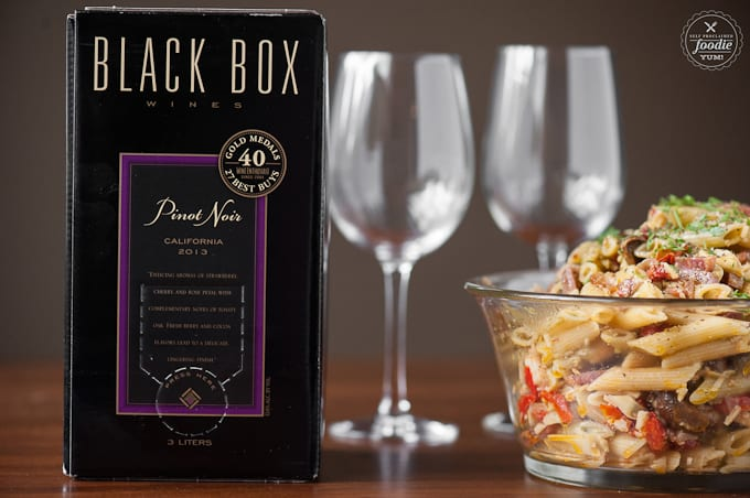 box of wine with glasses and pasta salad