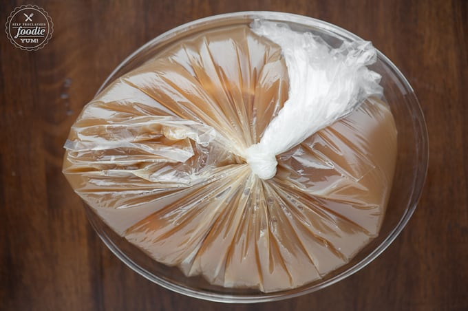plastic bag with pork roast in apple cider brine