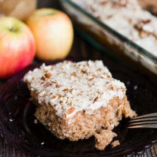 applesauce cake with brown butter frosting on plate with two apples and a jar of applesauce