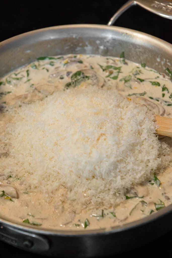 adding parmesan to homemade alfredo sauce
