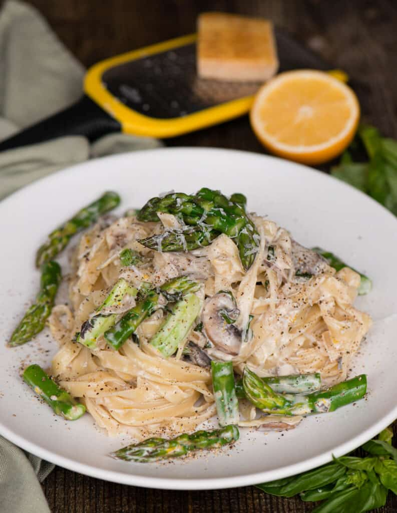 plate of Fettuccine Alfredo with mushrooms and asparagus