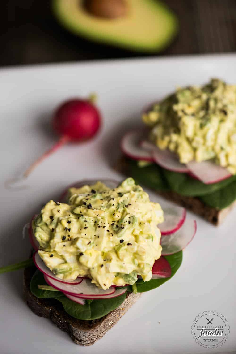 egg salad with avocados on toast with radish and spinach