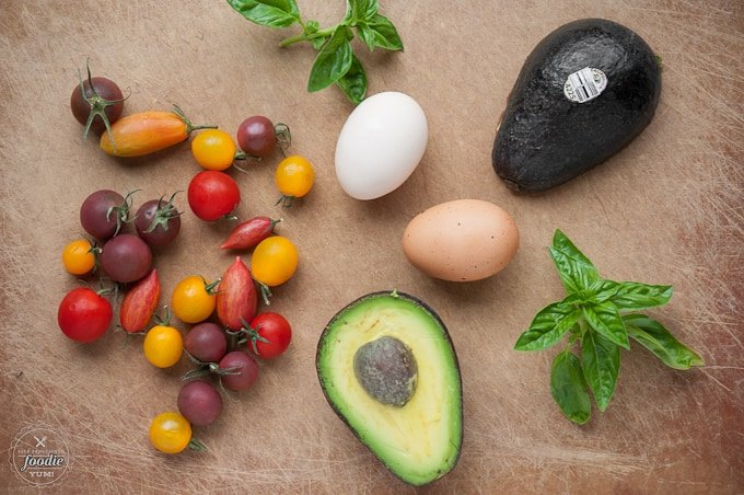 Looking for a rich and delicious breakfast that is also healthy and gluten free? These Avocado Eggs with Warm Basil Tomatoes are a must-make recipe.