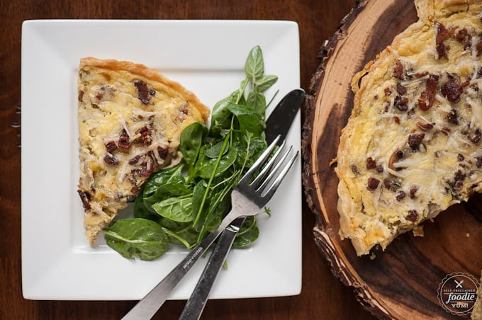 A plate of Quiche Lorraine with greens on the side