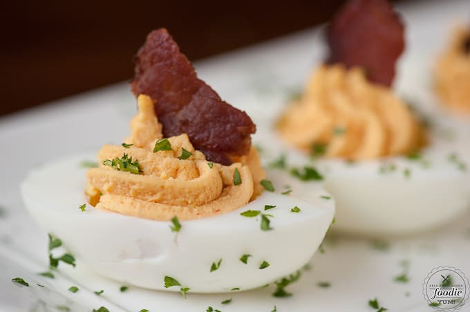 a close up of a bacon sriracha deviled egg