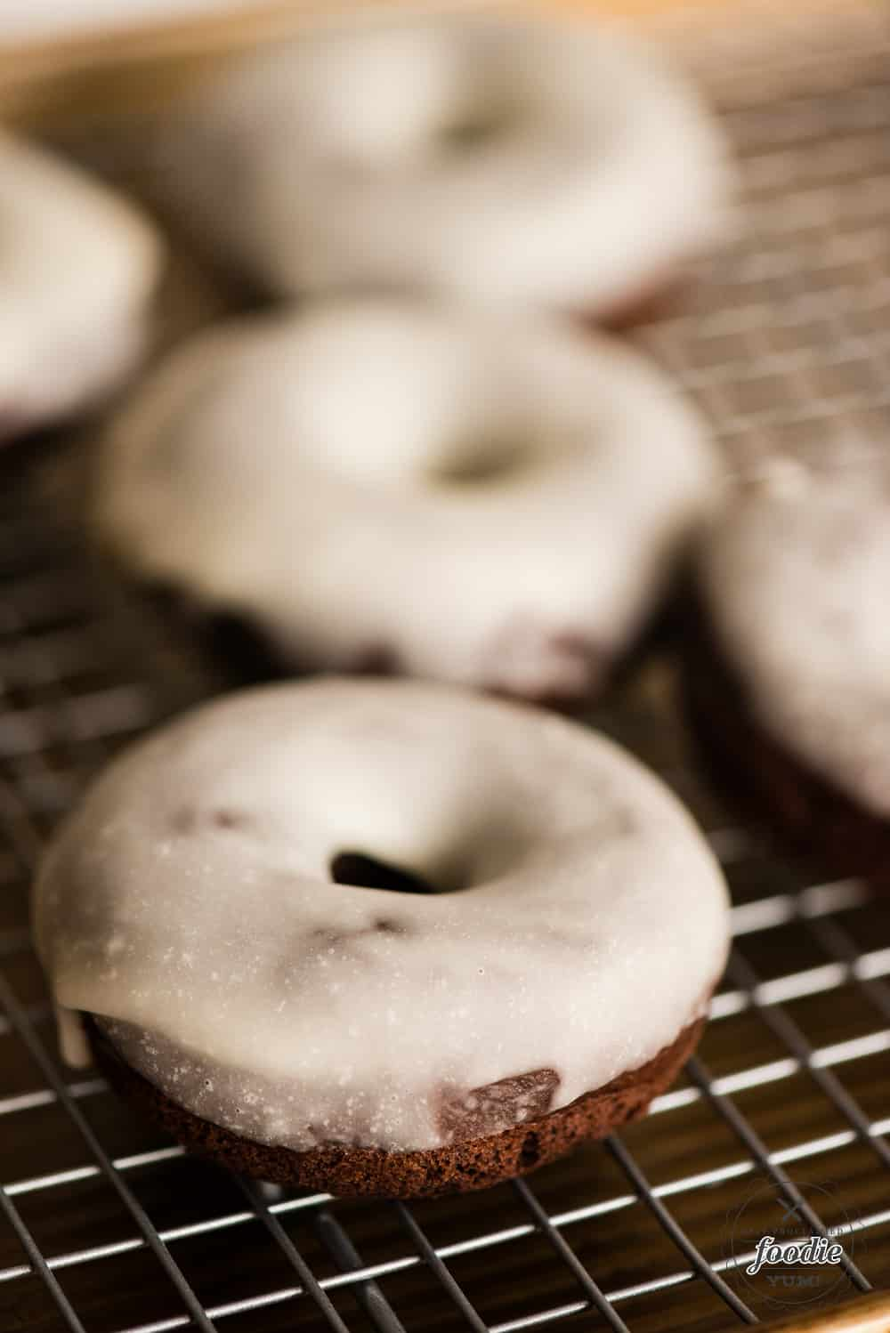 A close up of a baked chocolate glazed donut