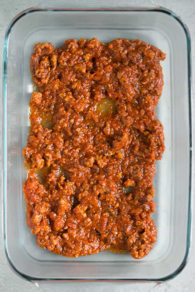marinara sauce and italian sausage in casserole dish