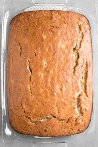 golden brown baked banana cake in glass baking dish