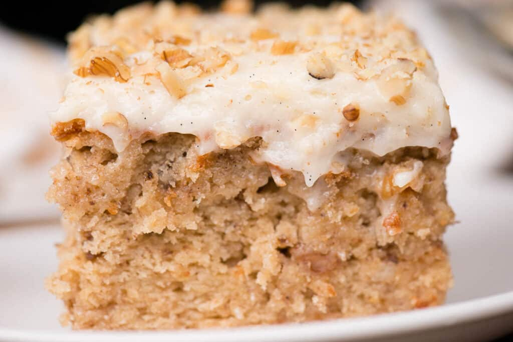 close up of frosted banana walnut cake