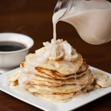 pouring sweet coconut syrup on stack of banana pancakes