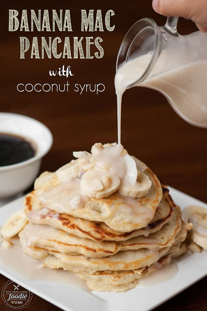 pouring coconut syrup on pancakes with banana and macadamia nuts