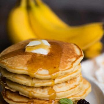 banana pancakes on plate with butter and syrup