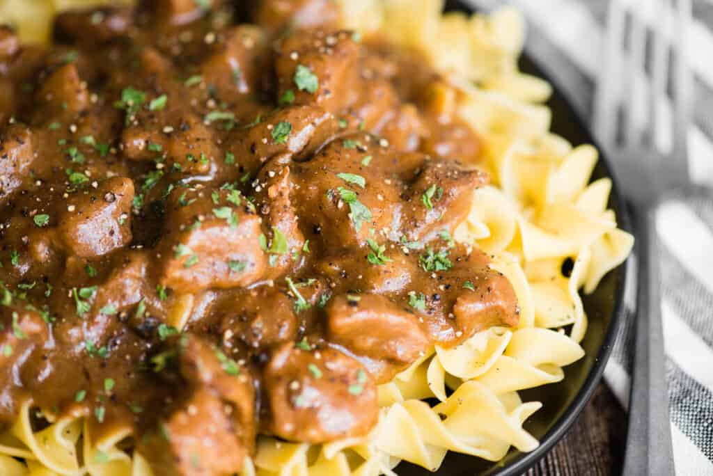 plate of butter noodles with beef stew meat and gravy