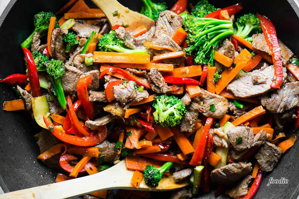 top view of Beef Stir Fry with vegetables in wok with wooden spoons
