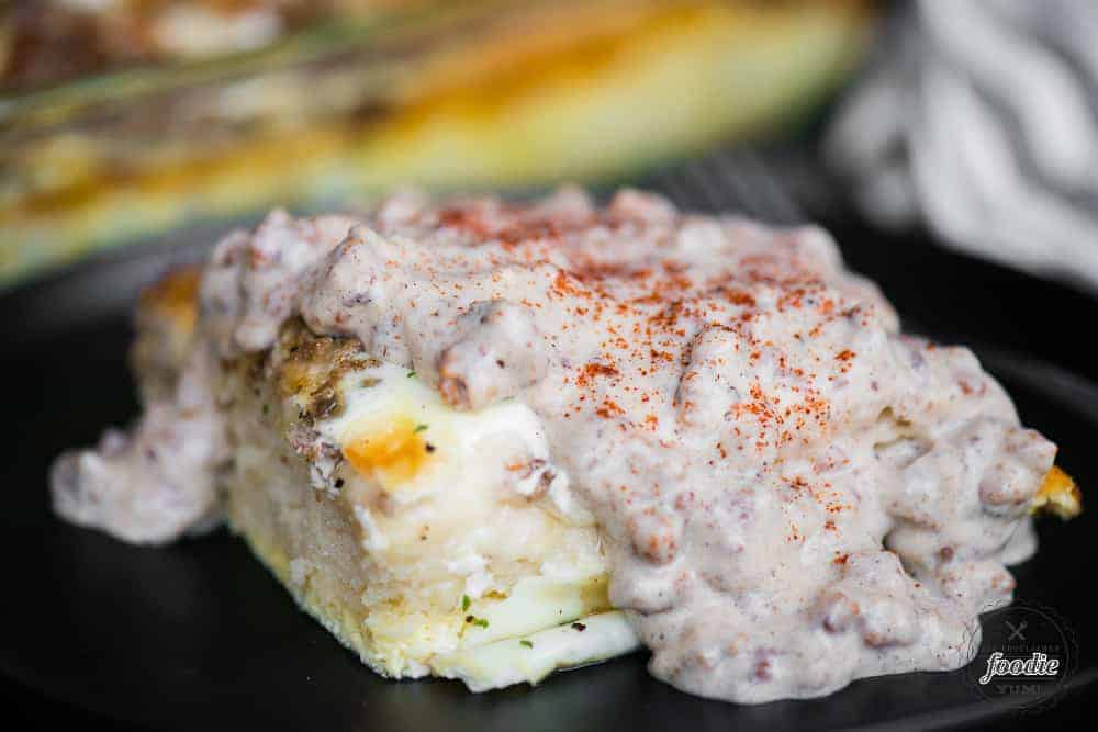 biscuits and gravy casserole made with homemade biscuits eggs cheese and topped with country sausage gravy