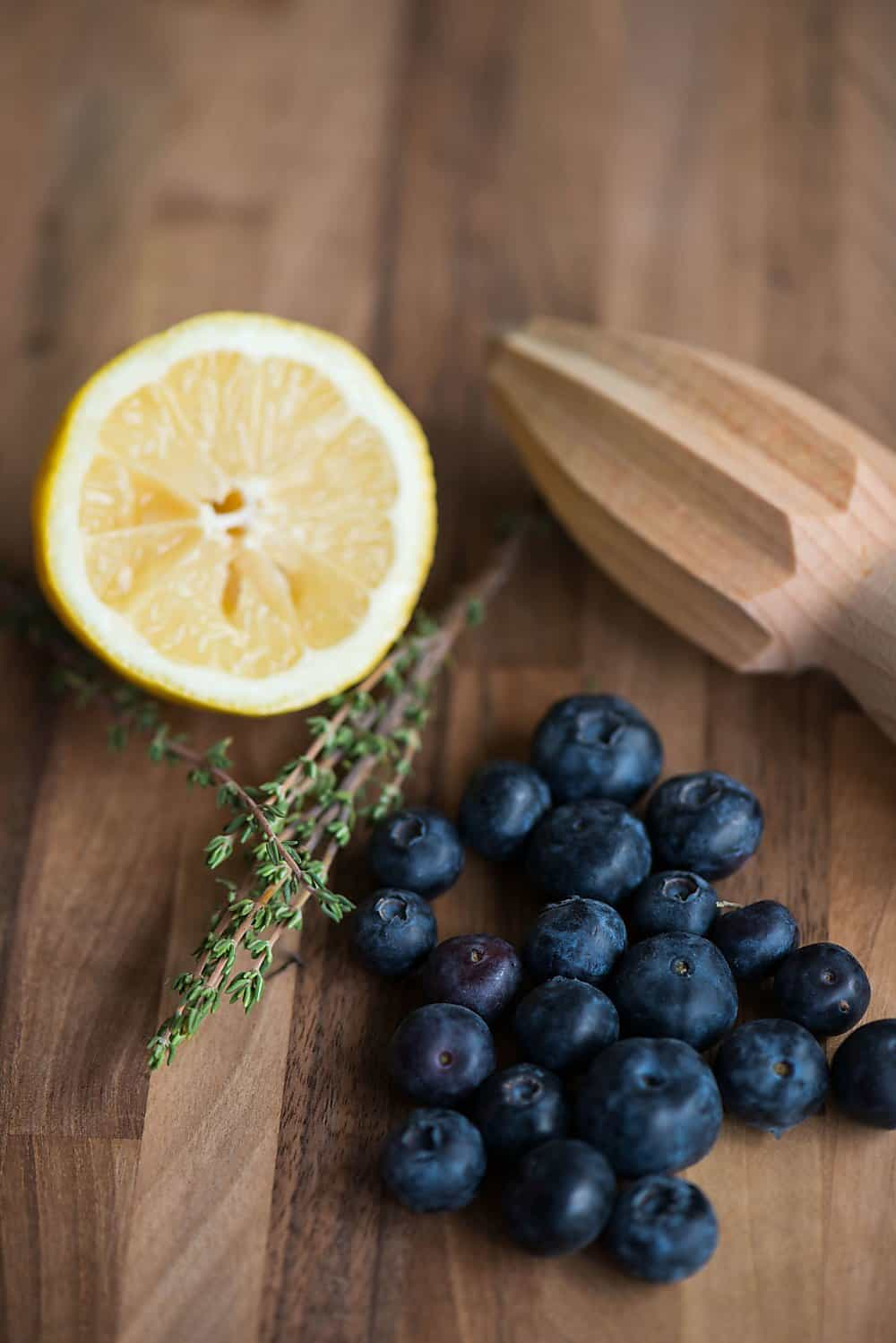 lemon, blueberries, and thyme on a wooden cutting board