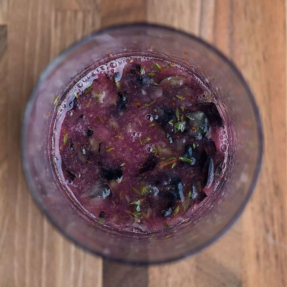 mashed blueberries and thyme in a glass