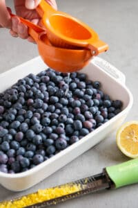 squeezing lemon juice onto fresh blueberries