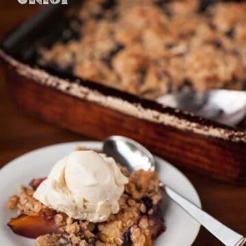 blueberry peach crisp on plate with vanilla ice cream