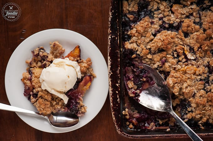 bowl of blueberry peach crisp topped with vanilla ice cream