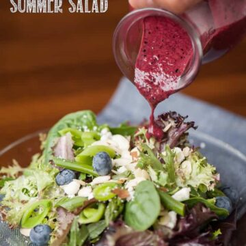 summer salad with blueberry vinaigrette being poured