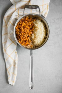roasted butternut squash and parmesan on top of risotto in pan