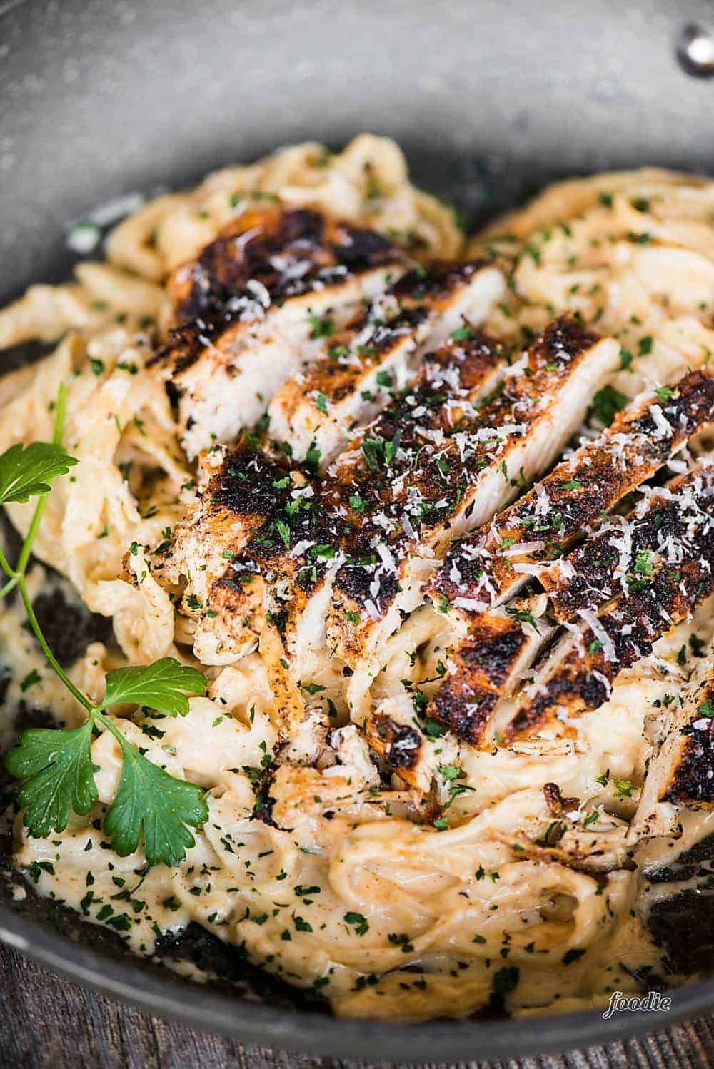 sliced blackened cajun chicken slices over fettuccine alfredo