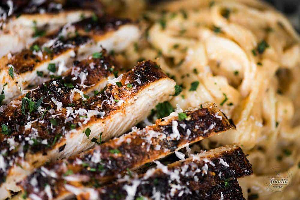 a close up of sliced cajun chicken over pasta