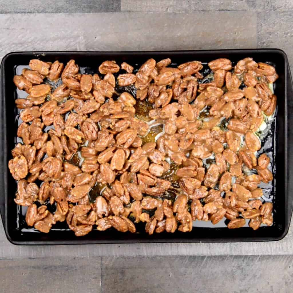 pecans coated in egg white and sugar on baking sheet